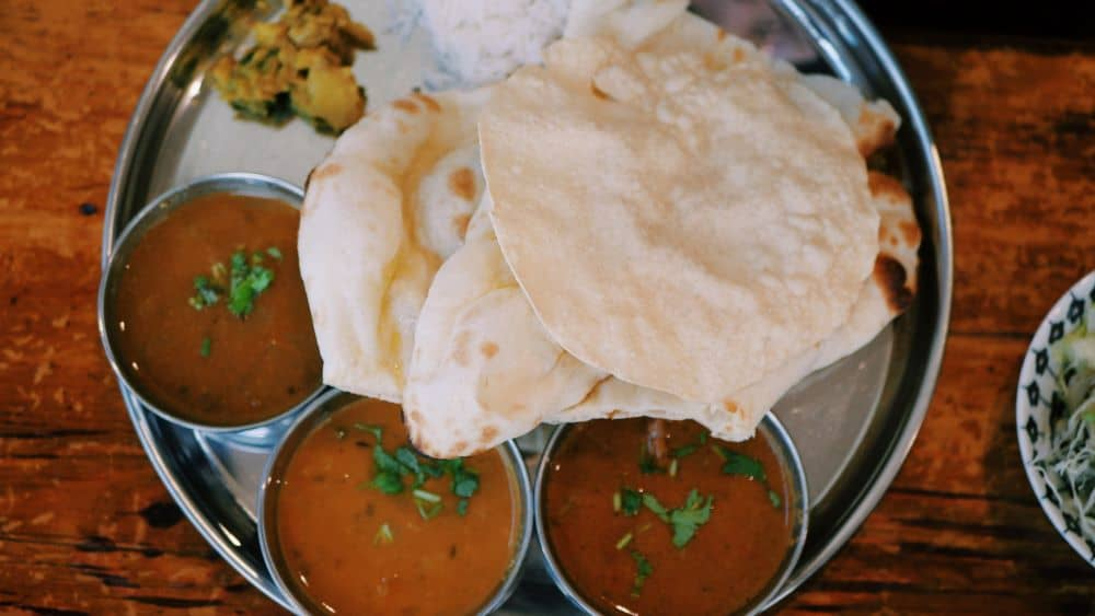 THE BEST THINGS TO DO IN DELHI, INDIA - A COMPLETE TRAVEL GUIDE TO INDIA'S HISTORIC CAPITAL featured by  The Common Traveler; Image: plate with Indian food