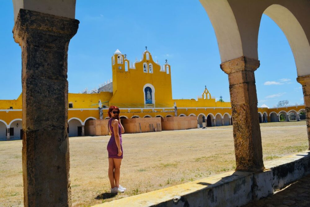 Mexico's Pueblos Magicos Worth Visiting by The Common Traveler: Image of woman in front of yellow building in Izamal | Pueblos Magicos Mexico by popular US international blog, The Common Traveler: image of a woman at Izamal, Yucatan.