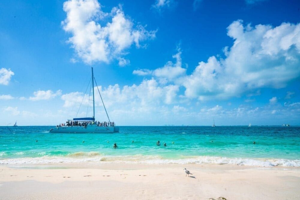 Mexico's Pueblos Magicos Worth Visiting by The Common Traveler: Image of sail boat and swimmers on beach in Isla Mujeres |Pueblos Magicos Mexico by popular US international blog, The Common Traveler: image of Isla Mujeres, Quintana Roo.
