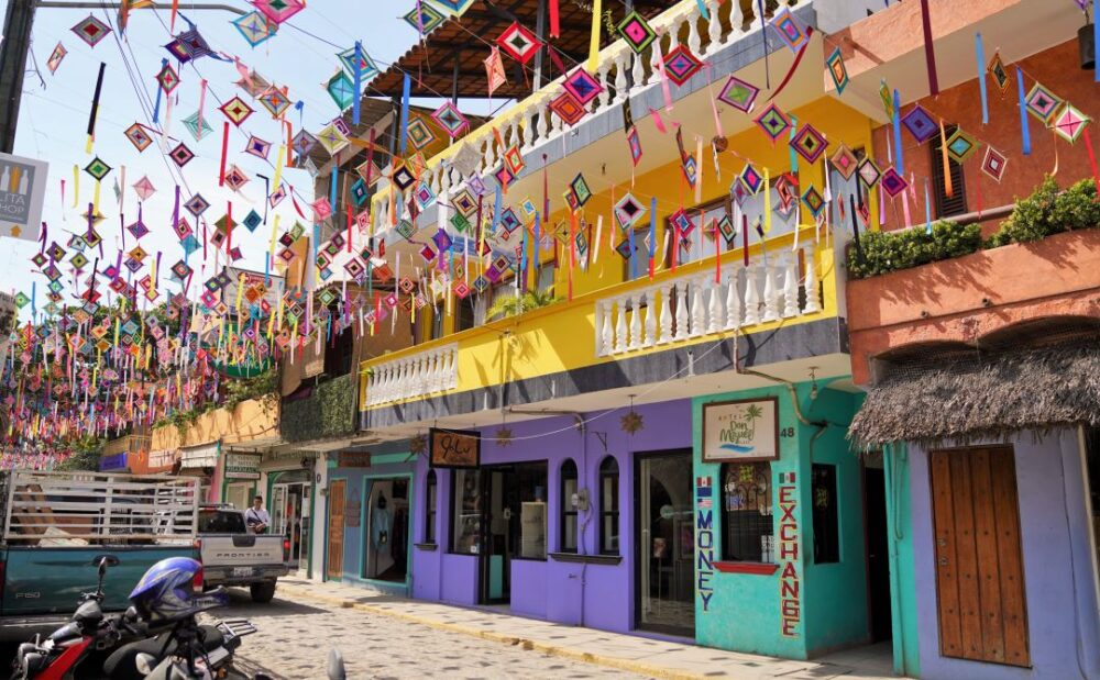 Mexico's Pueblos Magicos Worth Visiting by The Common Traveler: Image of colorful buildings and flags over street in Sayulita. |Pueblos Magicos Mexico by popular US international blog, The Common Traveler: image of Sayulita, Nayarit.