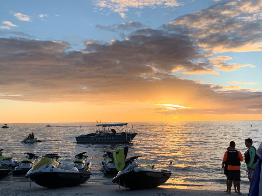BEST THINGS TO DO IN BONITA SPRINGS, FL featured by top US travel blogger, The Common Traveler: image of jet skis on shore at sunset on Bonita Beach, FL |Bonita Springs FL by popular US travel blog, The Common Traveler: image of jet skis and a pontoon boat in the ocean with an orange sunset in the background.