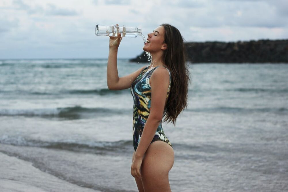 Image: woman in bathing suit drinking water from a water bottle |Travel Workout Equipment by popular US international travel blog, The Common Traveler: image of a woman standing by the ocean and drinking from a collapsible water bottle.