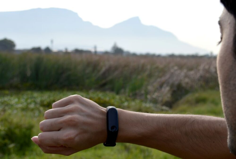 Image: forearm with fitness tracker with countryside in background |Travel Workout Equipment by popular US international travel blog, The Common Traveler: image of a man looking at a fitness tracker.
