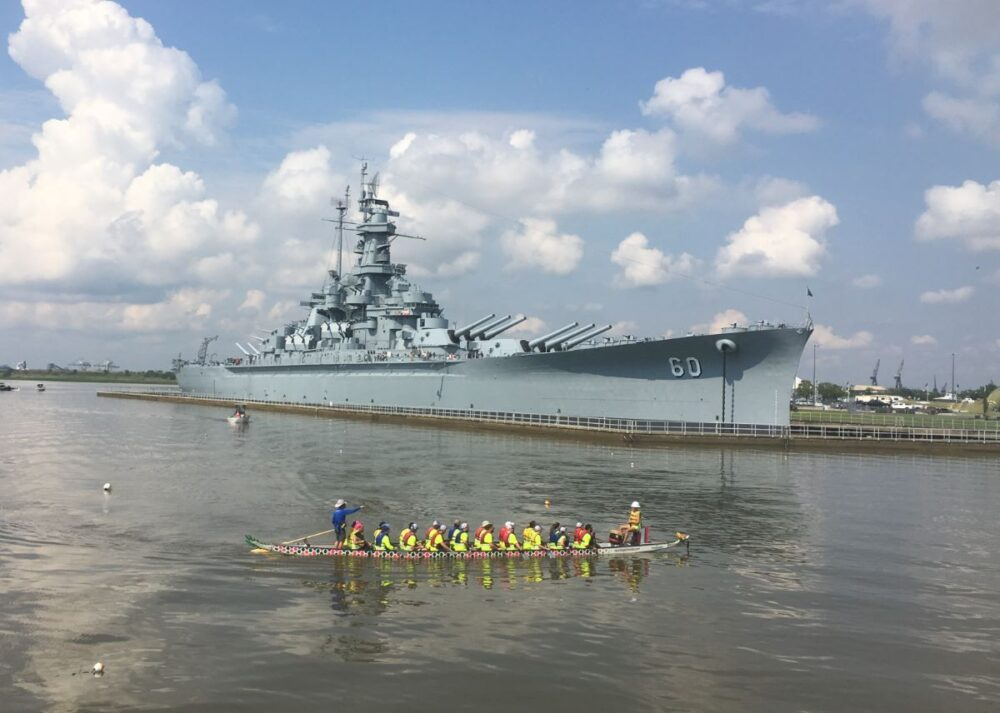 Best Day Trips from New Orleans | The Common Traveler | image: rowers in front of USS Alabama battleship |New Orleans Day Trips by popular US travel blog, The Common Traveler: image of a boat of rowers next to the USS Alabama.