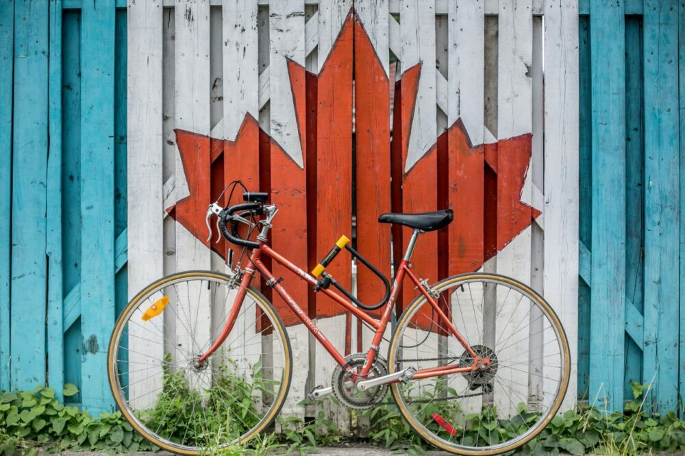 12 Amazing Canada Outdoor Activities | The Common Traveler | image: red bicycle in front of fence painted with Canada flag maple leaf |Canada Outdoor Activities by popular US international travel blog, The Common Traveler: image of a bicycle in front of a fence with a Canada flag maple leaf painted on it.