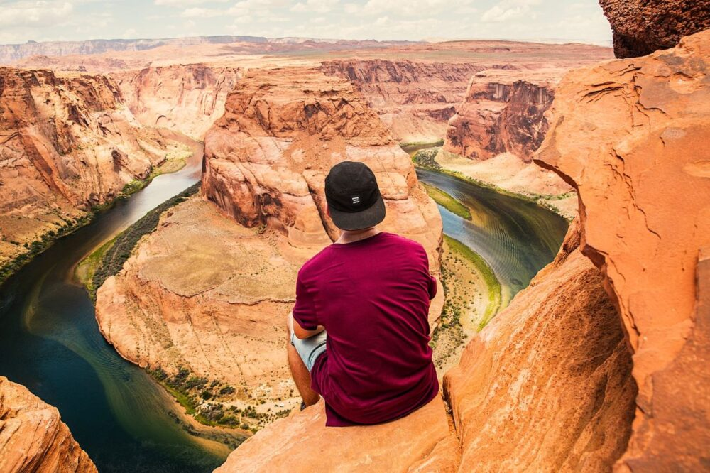 Tips for Staying Safe While Traveling | The Common Traveler | man sitting on rock in front of Grand Canyon | Traveling Alone by popular US travel blog, The Common Traveler: image of a man sitting on rock in front of the Grand Canyon.