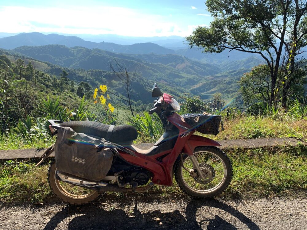 Six Amazing Motorcycle Rides Around the World | The Common Traveler | image: red motorcycle in front of hills and valleys in Laos |Motorcycle Rides by popular US international travel blog, The Common Traveler: image of a motorcycle on a road in the hills of Laos.