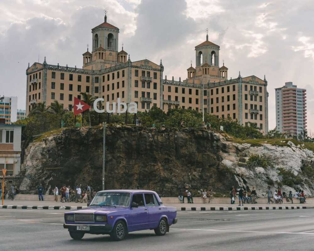 Six Amazing Motorcycle Rides Around the World | The Common Traveler | image: Havana yellow building with Cuba spelled out in front |Motorcycle Rides by popular US international travel blog, The Common Traveler: image of a purple car in front of a yellow Havana building with a large Cuba sign in front of it.