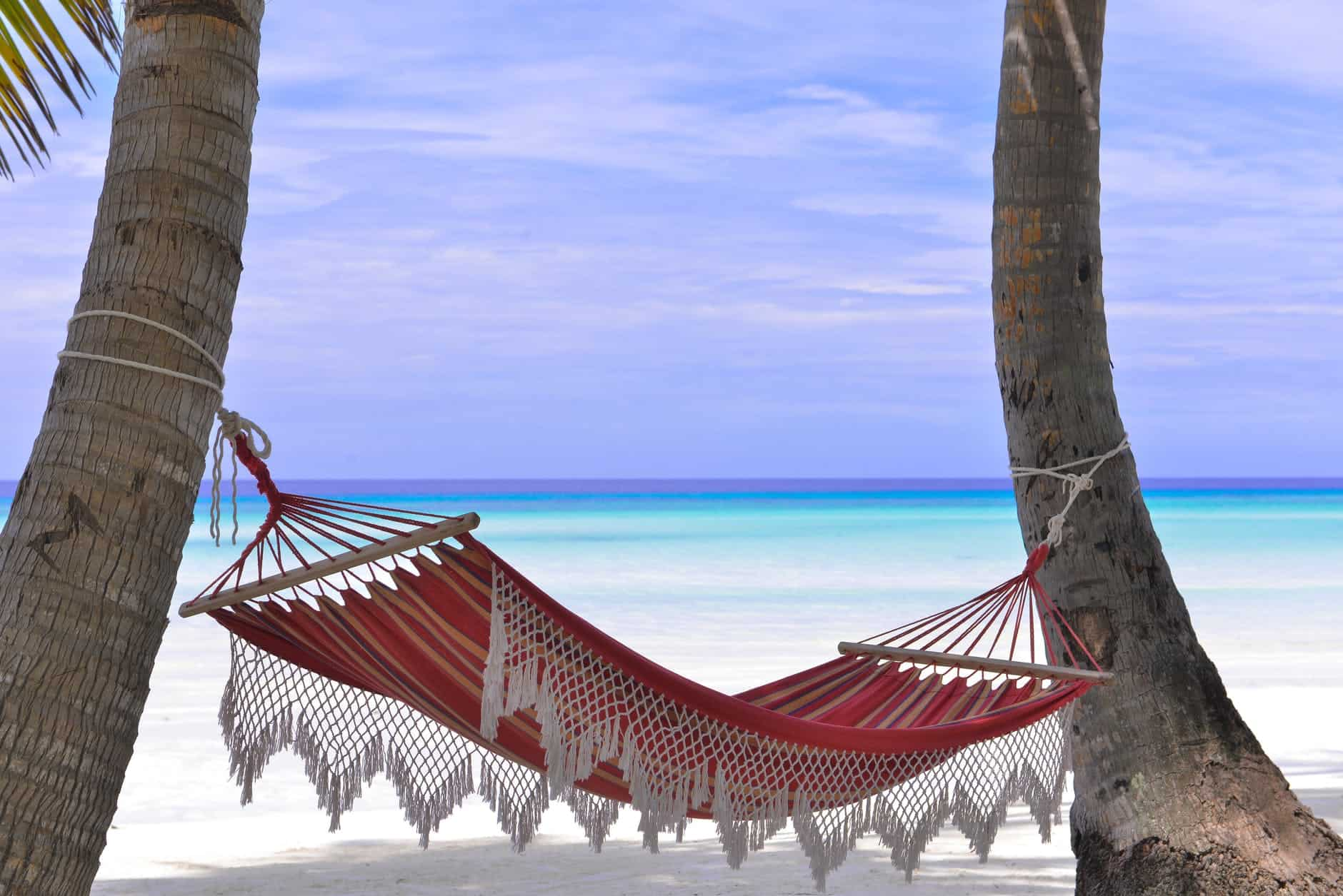Tips for when you travel to a hotter climate | The Common Traveler | image: red hammock tied between two trees