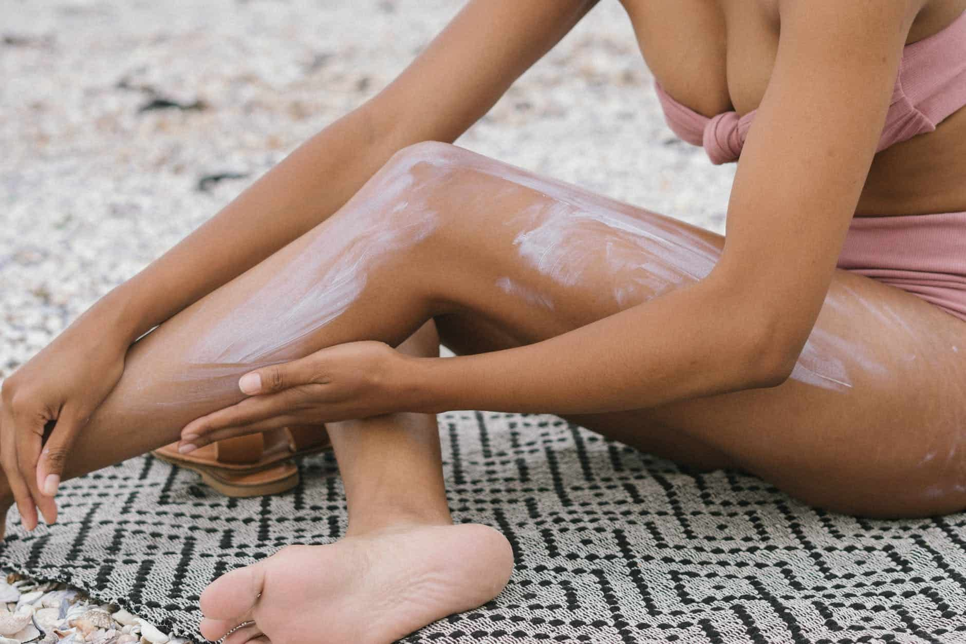 Tips for when you travel to a hotter climate | The Common Traveler | woman seated on textile applying sunscreen | Hot Climate by popular US international travel blog, The common Traveler: image of a woman wearing a pink two piece swimsuit and applying sunscreen to her leg.
